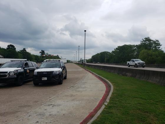 Texas DPS troopers at the Texas-Louisiana border while Louisiana travelers pass by.
