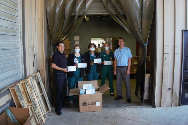 Moses Ceciliano, far left, and Mike, far right, of Great China Restaurant pose with 1,000 medical masks they donated to a CHRISTUS warehouse in Beaumont on April 13.